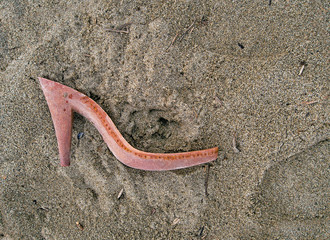 Pollution or drowned - plastic female shoe remains on beach