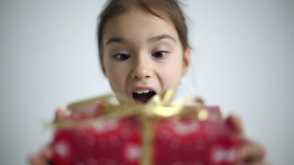 Female child receives a gift surprised and glad.