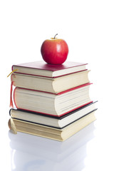 Books tower with red apple isolated on white background