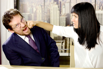 Woman hitting business man boss in office