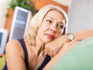 Sad  mature woman sitting on couch