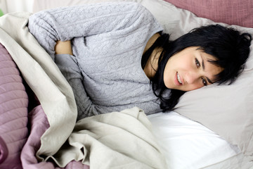 Woman with strong menstruation stomach ache lying in bed