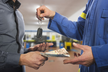 dealer hands over the keys of the car to the customer