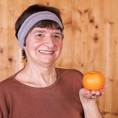 femme avec mandarine dans la main
