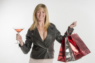 Woman with glass of bubbly holding shopping bags