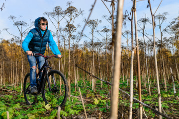 Cyclist extreme riding bike through dried bushes in autumn