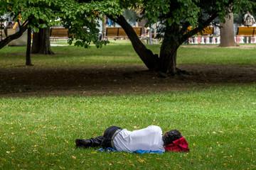 Mann schläft im Park
