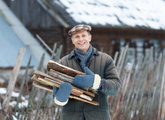 Happy man holding an armful of firewood