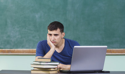 Sad upset overworked man studying in front of laptop