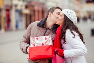 Young man kissing his girlfriend and giving her presents