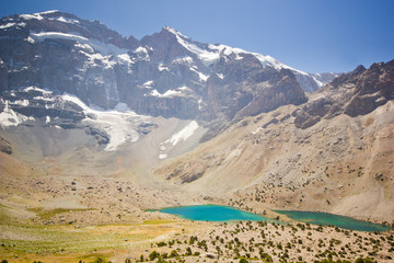 two mountain lakes with different colour surrounded by high