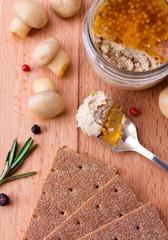 Chicken pate in jar and crispbread on wood cutting board