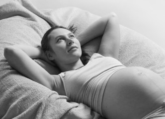 Pregnant woman lying on bed. Black and white photography.