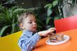 Child touching cake