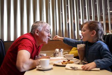 Grandchild feeds his grandfather