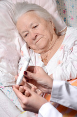 Medical nurse measuring the blood sugar level