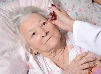 Nurse dripping eye drops to old woman
