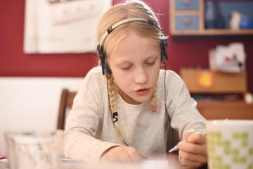 Kleines Mädchen mit Kopfhörern macht Hausaufgaben