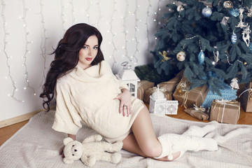 pregnant woman with dark hair posing beside a Christmas tree