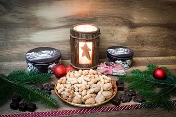 Weihnachtliche Dekoration, Nussteller vor Holzwand mit Laterne