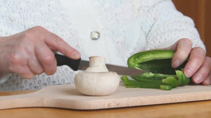 An old woman is slicing pepper and preparing vegetarian dish