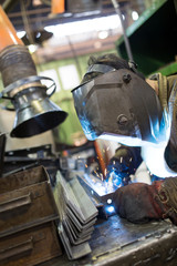 Industrial worker welder welding metal at factory workshop