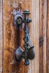 Old iron knoker on an old metal door