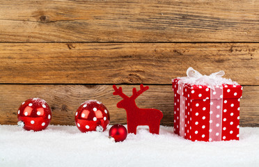 red gift for christmas on a wooden background with snow..