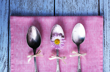 Metal spoons on pink napkin on wooden background