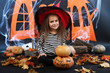 Little girl Witch in hat with pumpkins