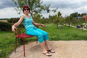 Frau sitzt auf einer roten Gartenbank