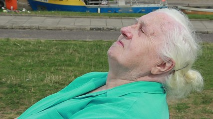 Old woman is relaxing and exposing her face to the sun.