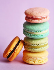 Assortment of gentle colorful macaroons on color background