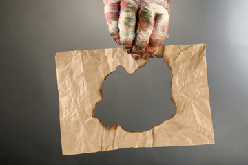 Hand of mummy holding old paper on gray background