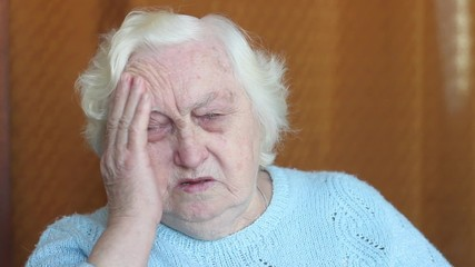 Old woman suffering from headache.
