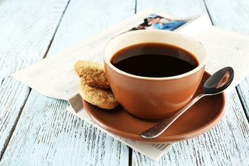 Cup of coffee with newspaper on color wooden background
