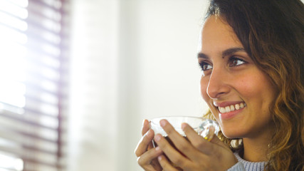 Attractive young woman holding a hot drink and smiling
