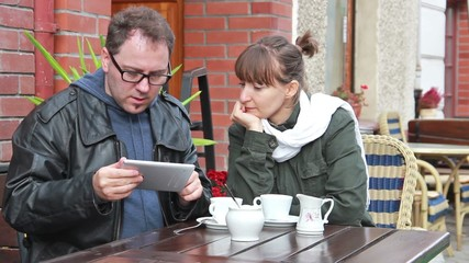 Young people with a tablet in the outdoor cafe