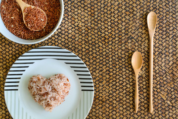 Heart shape brown rice with wooden spoon