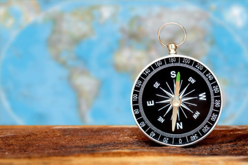 Close up compass on wood with blur map background