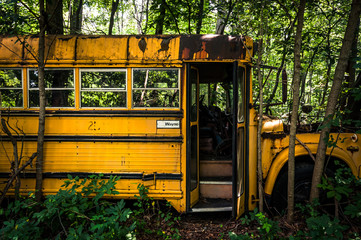 A rusty old school bus in a junkyard.
