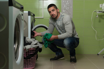 Young Man Putting A Cloth Into Washing Machine