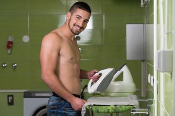 Naked Man Ironing Clothes In A Utility Room