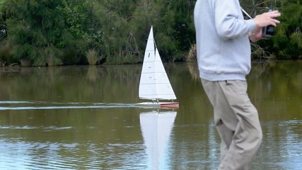 People racing remote control sailing wooden yachts