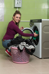 Young Woman Doing Housework Laundry