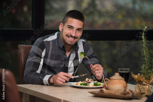 Young Handsome Man Eating At A Restaurant