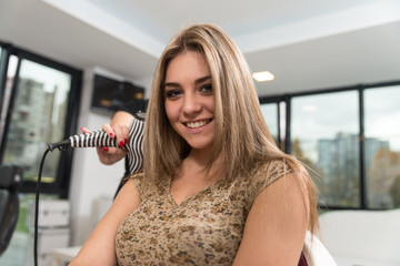 Hairdresser Doing Haircut For Woman In Hairdressing Salon