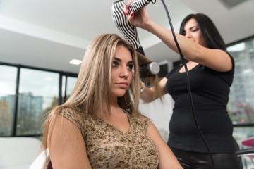 Hair Stylist Using Dryer On Woman In Salon