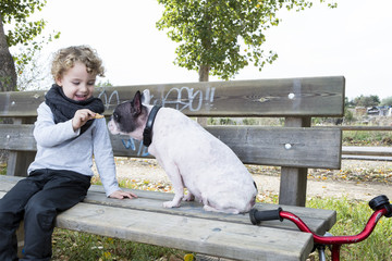 child giving his dog a biscuit