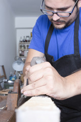 luthier using a hand planer